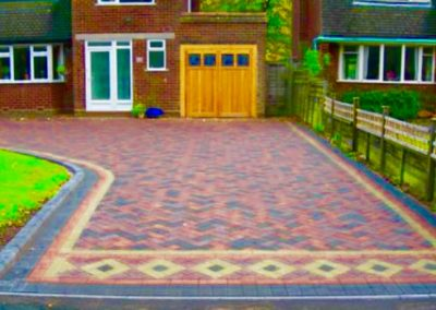 Block paving driveway with patterns leading to garage
