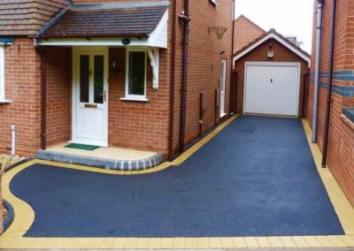 Dark tarmac driveway with a light brick border