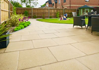 Large garden with sandstone paving